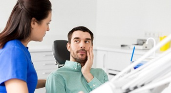 A male patient holding his cheek and looking at his dentist