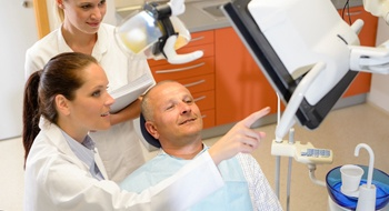 A male patient in the dentist chair looking at a screen shown by the dentist