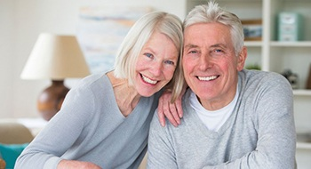 elderly couple smiling and wearing matching gray sweaters