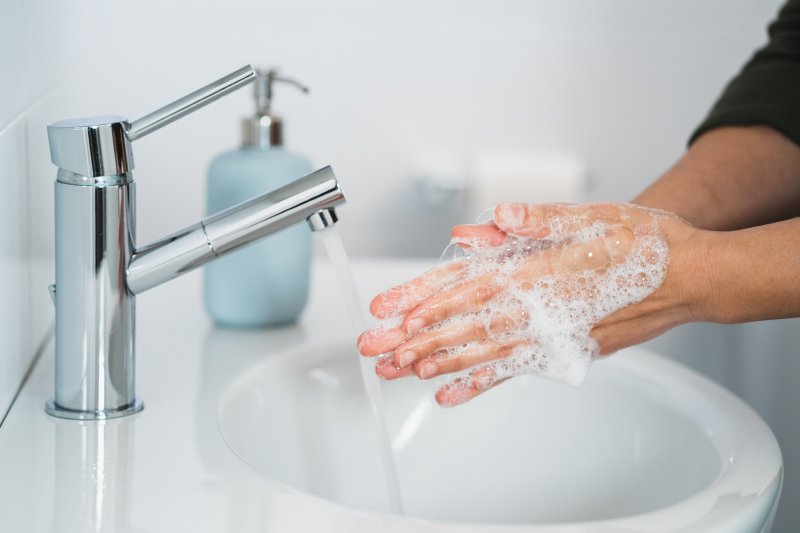 Woman washing hands with soap and water
