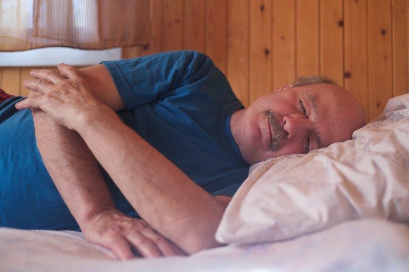 Senior man sleeping on side with sleep apnea in Weatherford