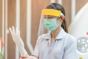Weatherford dentist with face shield puts on gloves in preparation