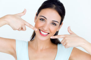 Young woman pointing to healthy beautiful smile