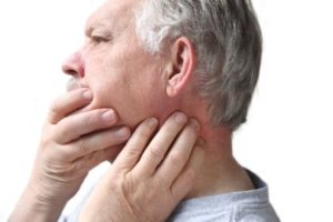 A man in pain holding his jaw