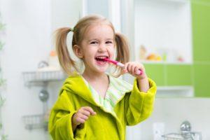 girl smiling brushing her teeth